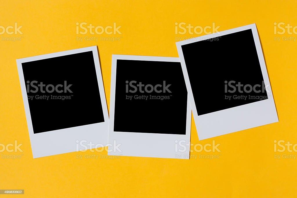 Polaroid photo prints isolated on yellow stock photo