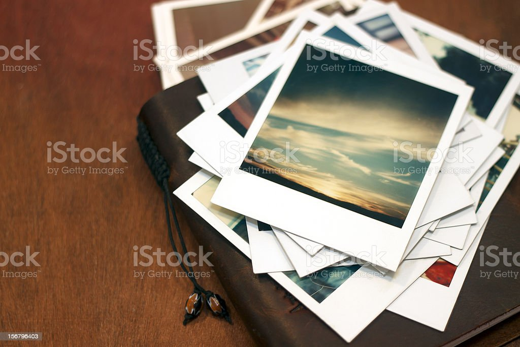 Polaroid pictures of sunset on leather journal stock photo