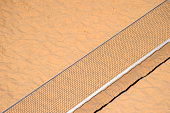 Pole aerial image of a beach volleyball court. Includes an overhead perspective of the net and sand texture