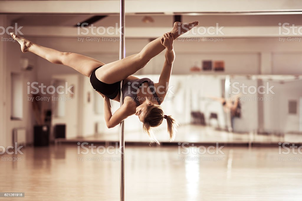 Pole dancer exercising ceiling splits in a dance studio. stock photo