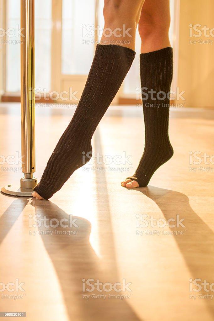 Pole dancer\'s legs in black knee socks performing on floor in dance...