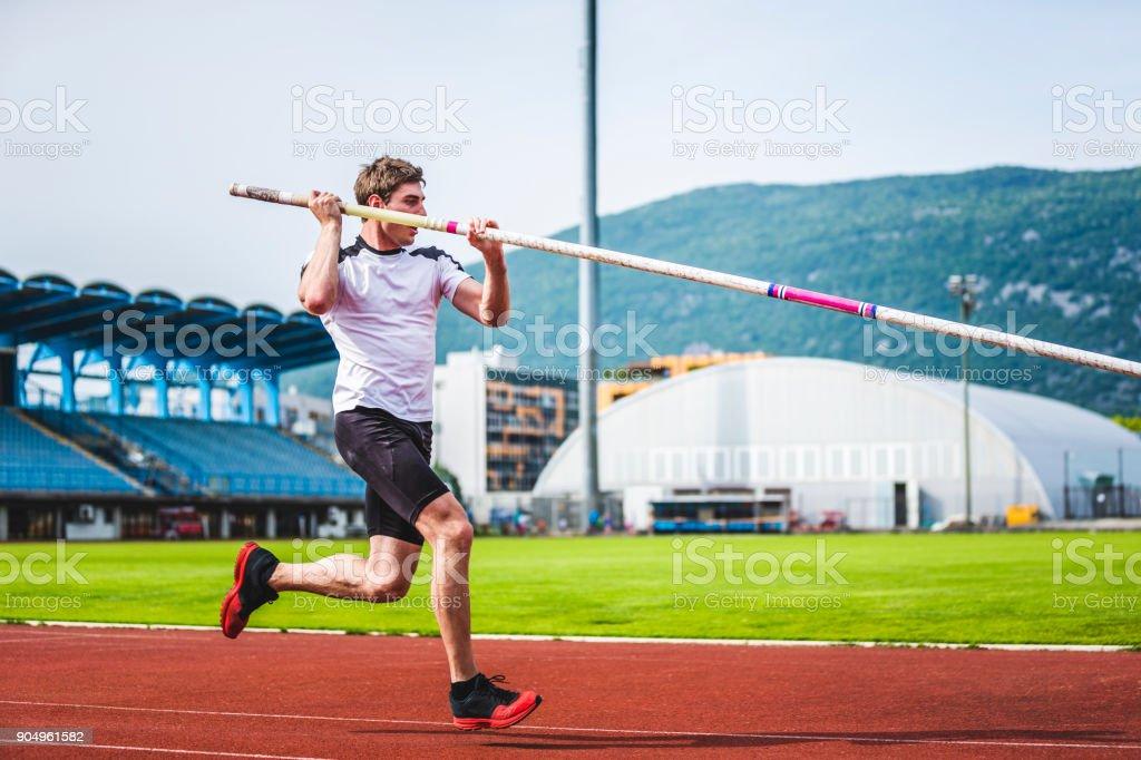 Pole vault male athlete running with pole stock photo