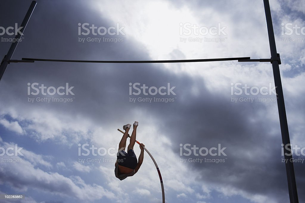 Pole vaulter in mid-air stock photo