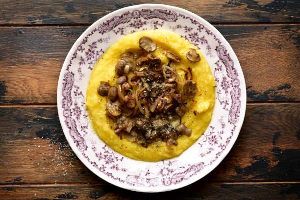 튀긴 버섯, 파마산 치즈, 카라멜 화 된 양파를 곁들인 폴렌타 - 폴렌타 죽 뉴스 사진 이미지