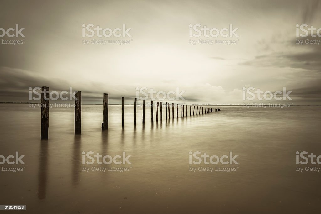 Poles in the at the beach in sepia stock photo