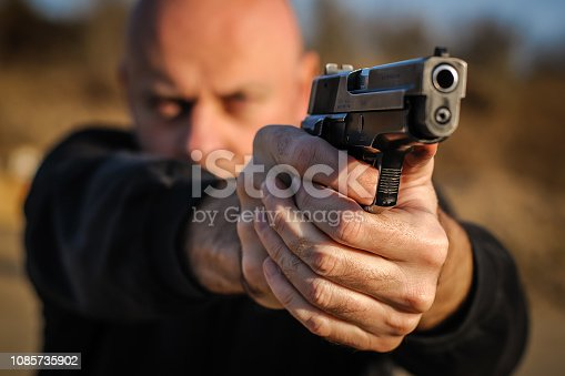 Police agent and bodyguard pointing pistol to protect from attacker. Gun point aiming front view outdoor