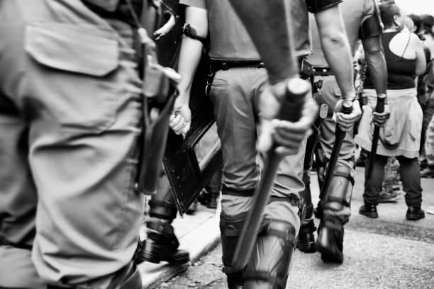 politie en wapenstokken - exploitatie stockfoto's en -beelden