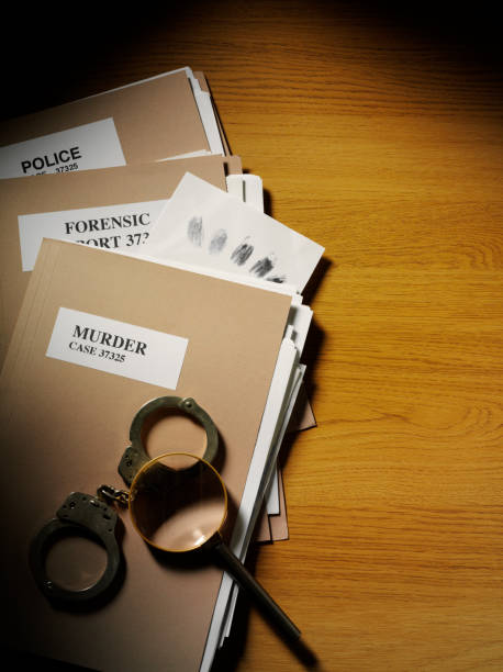 police and forensic paper files, a magnifying glass with handcuffs - murder mystery stock photos and pictures