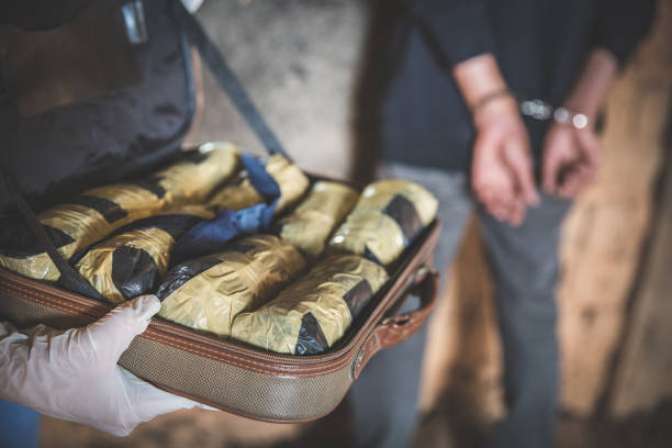 Police arrest drug trafficker with handcuffs. Law and police concept.  World Anti-drug Day Police arrest drug trafficker with handcuffs. Law and police concept.  World Anti-drug Day smuggling stock pictures, royalty-free photos & images