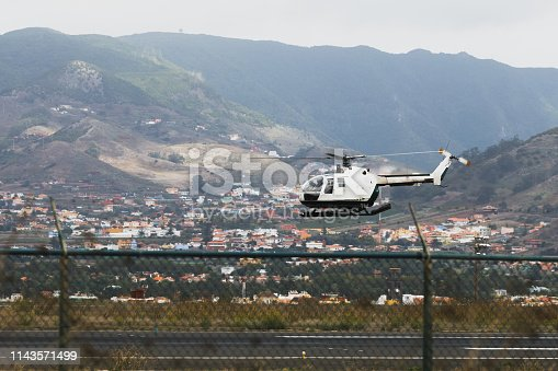 police aviation helicopter above the airstrip, mountain background