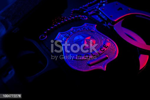 istock Police badge, handcuffs and pistol at night in police lights 1004772276