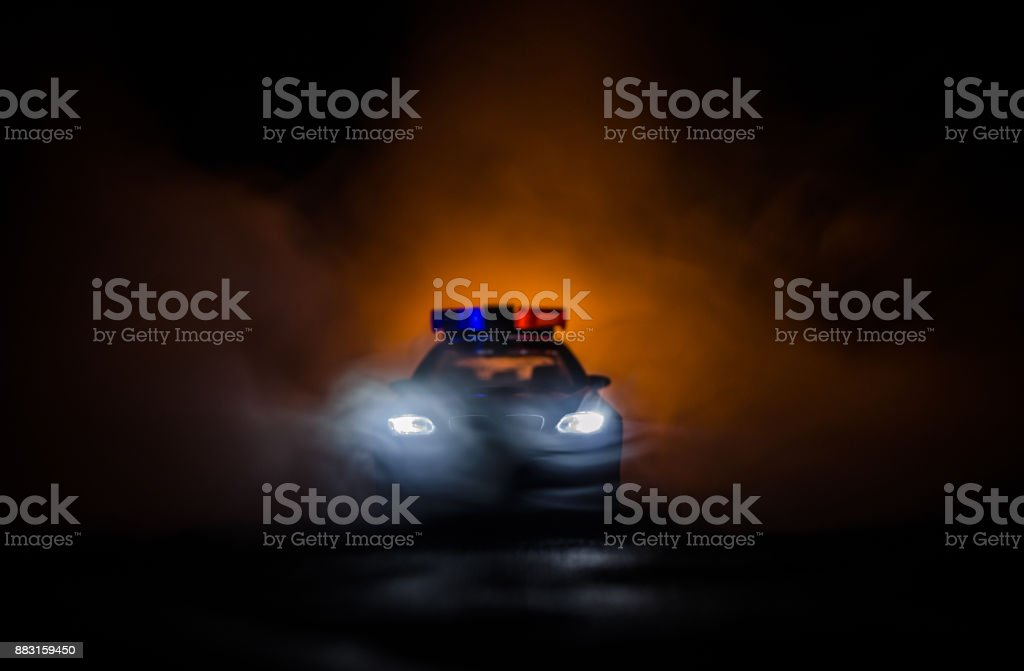Police car chasing a car at night with fog background. 911 Emergency response police car speeding to scene of crime stock photo