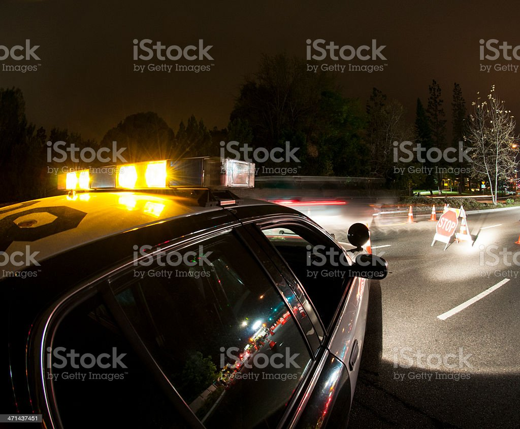 Police car illuminating stop sign stock photo