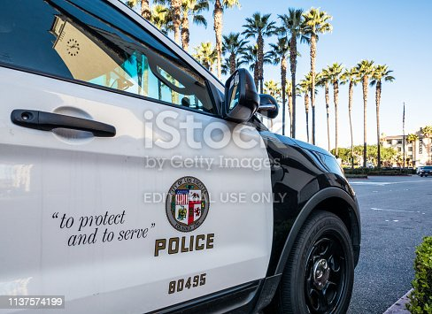 Los Angeles, USA - Close-up on the insignia and slogan of a LAPD vehicle, with the reflection of Union Station's tower visible in the car's window.
