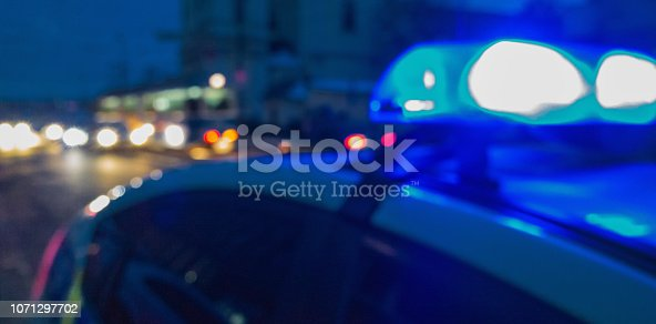 istock Police car lights in night time, crime scene. Night patrolling the city. Abstract blurry image. 1071297702