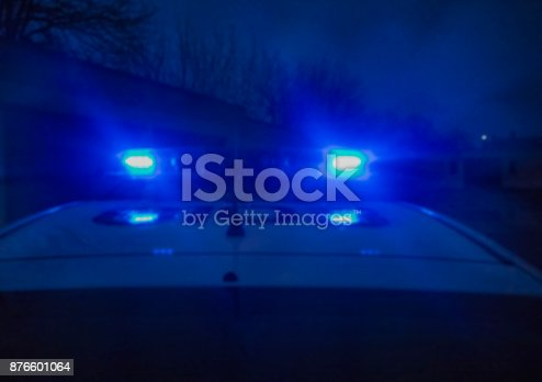 904615574 istock photo Police car lights in night time, crime scene. Night patrolling the city. Abstract blurry image. 876601064