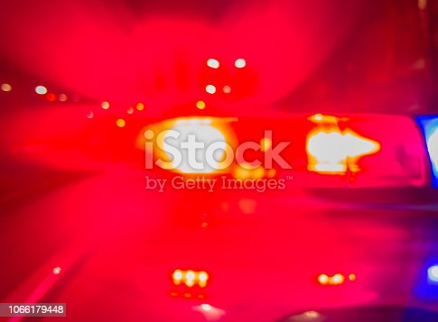 istock Police car lights in night time for crime news and accidents. Crime scene, night patrolling the city. Abstract blurry image. 1066179448