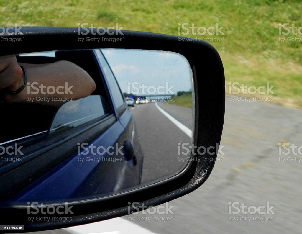 Police car motorcade in the rear view mirror stock photo