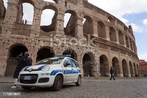 Rome / Italy - January 28, 2019: A police car stands in front of the amphitheater Colosseum (construction years 72-80), monuments of Ancient Rome with tourists nearby.