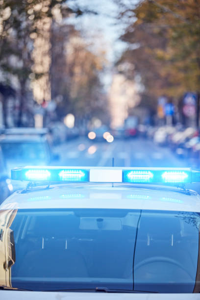 Police car with blue lights on the crime scene in traffic / urban environment. stock photo