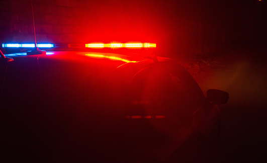 istock Police car with red and blue flashing lights on empty night street background, crime scene, night patrolling the city, fight against looting during quarantine. 1217090850
