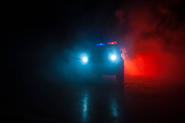 Police cars at night. Police car chasing a car at night with fog background. 911 Emergency response police car speeding to scene of crime. Selective focus – zdjęcie