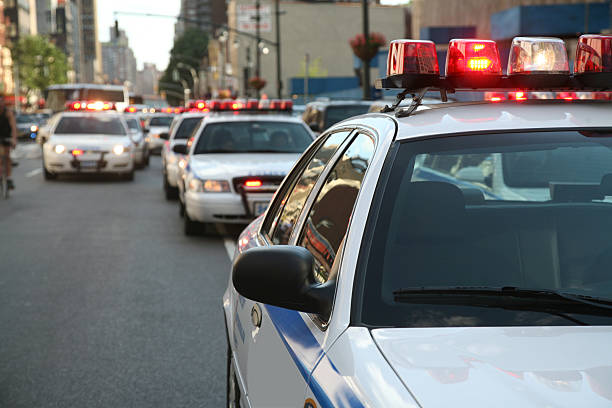 Police Cars On Street Row of police cars with flashing lights and sirens on the streets of Manahttan, New York City, New York, USA. medium group of objects stock pictures, royalty-free photos & images