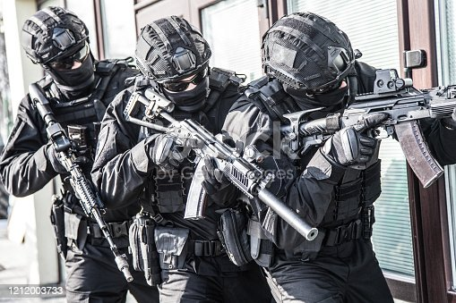 Police counter terrorist tactical unit, special reaction team in black blank uniforms with hidden identity, armed with assault rifles, moving in stack formation during terrorism response operation