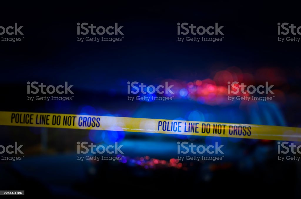 """Police Crime Scene A stock photo of a Police Line """"Do Not Cross"""" caution tape with a defocused police car with sirens flashing red and blue. Barricade Tape Stock Photo"""