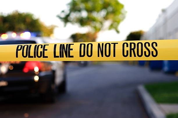 A police crime scene tape close-up A blurred police car in the background behind yellow crime scene tape.  tape stock pictures, royalty-free photos & images