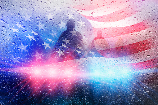 Police crime scene with lights and raindrops and american flag