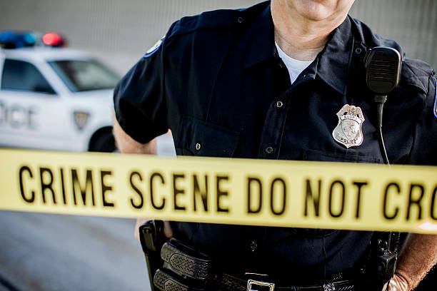 Police Detective at Crime Scene Image of a police detective at a crime scene in a back alley police uniform stock pictures, royalty-free photos & images
