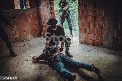 Group of man, special police forces in abandoned house, making an arrest.