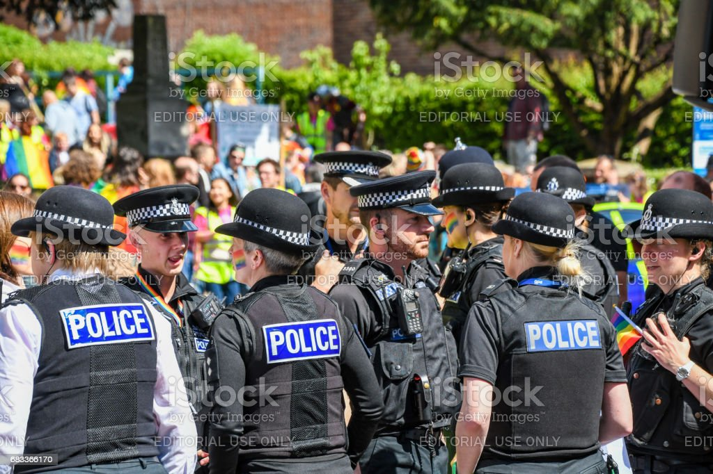 Police gather for Exeter Pride with rainbow face paint Uniformed officers from Devon Police force are taking part in Exeter Pride, some have rainbow face paint on. Crowds gather in the background. Parade through city centre. Community Stock Photo