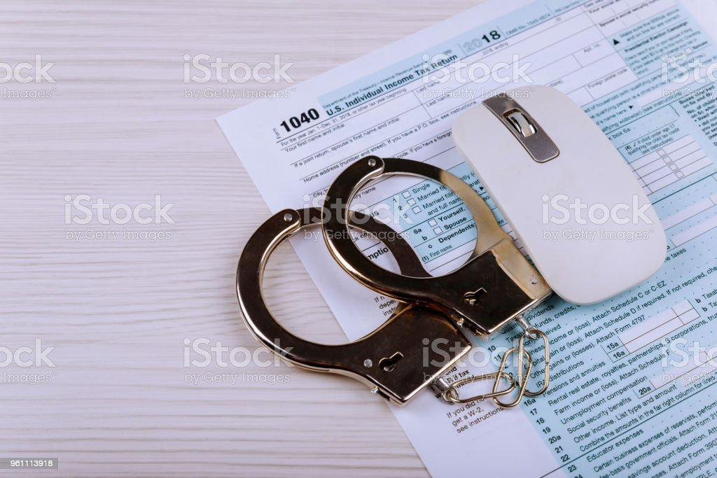 Police handcuffs lie on the tax form 1040. The concept of problems with the law in the aftermath of non-payment of taxes stock photo