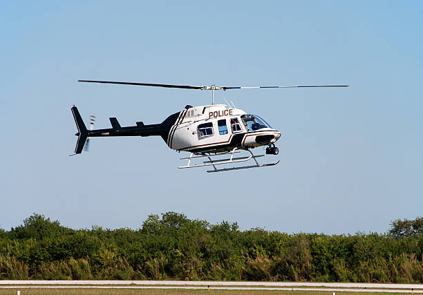 Police helicopter flying above a tree line on a sunny day stock photo