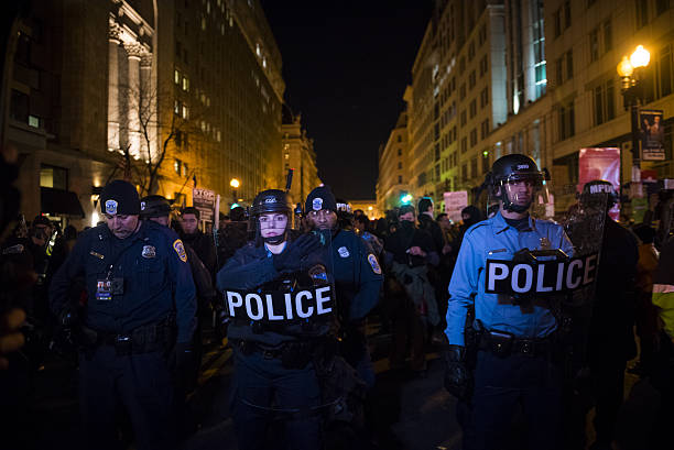 Police in Washington DC in riot gear Washington DC, USA - January 19, 2017: Washington Metropolitan Police stand on 14th Street holding shields during protest on the eve of President-elect Trump's inauguration. riot police stock pictures, royalty-free photos & images