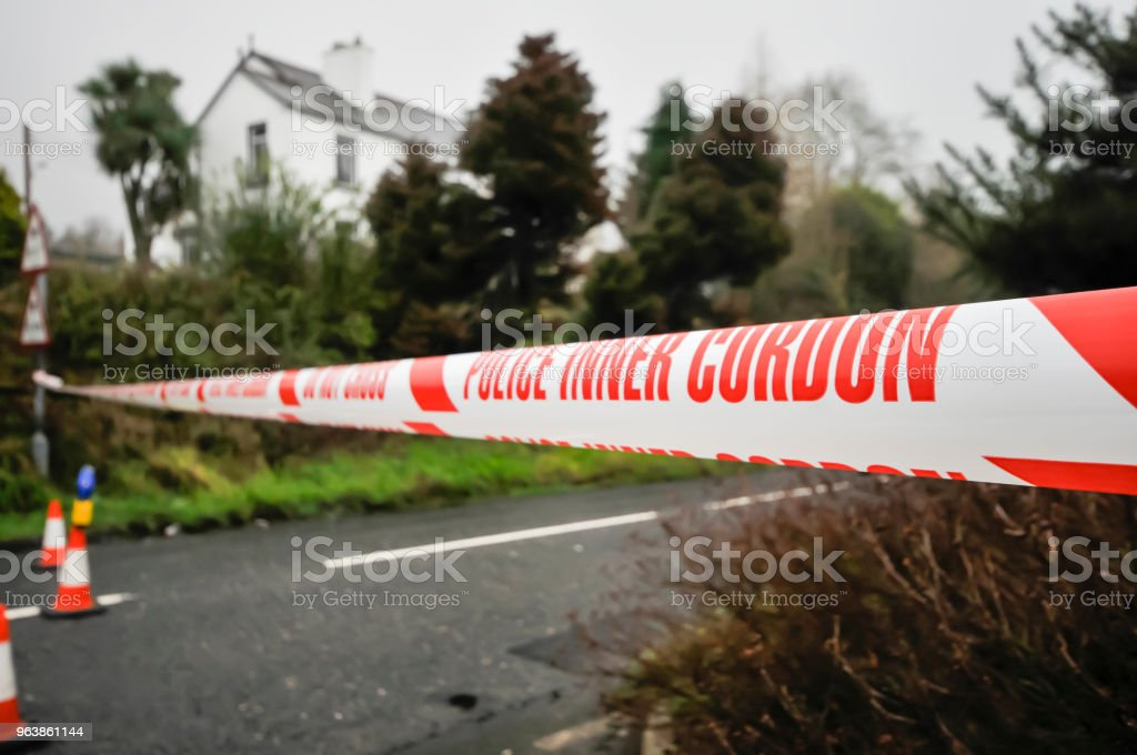"""Police """"Inner Cordon"""" tape is stretched across a road at the scene of a murder investigation. - Royalty-free Carrickfergus Stock Photo"""