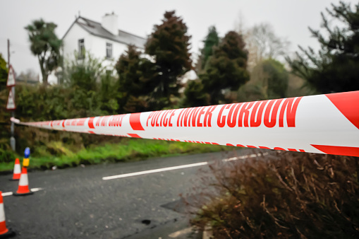 Police Inner Cordon Tape Is Stretched Across A Road At The Scene Of A Murder Investigation Stock Photo - Download Image Now