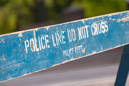 Police line, do not cross sign against a park background in New York City