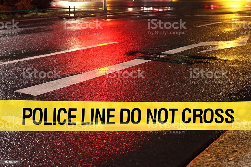 Police line do not cross: wet asphalt on city street stock photo