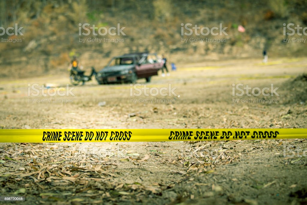 Polizei-Linie Klebeband mit unscharfen Strafverfolgungsbehörden und zerstörten Auto Hintergrund – Foto