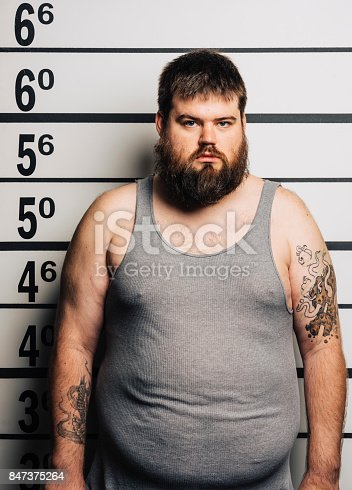 A man standing in front of a mugshot wall in a police station.