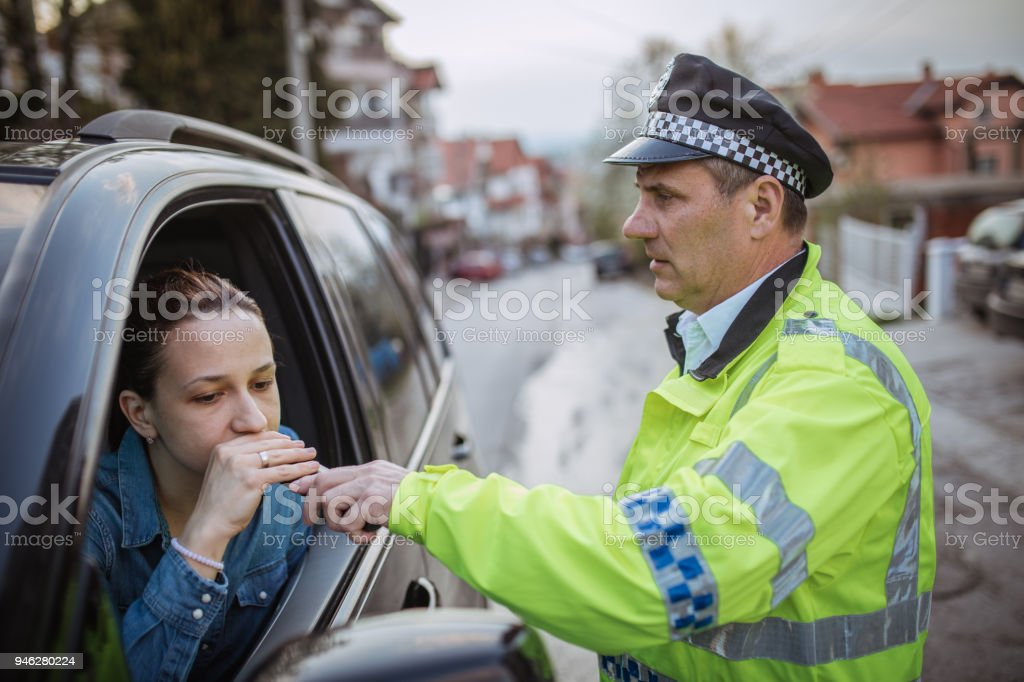 Police man giving woman an alcohol test stock photo