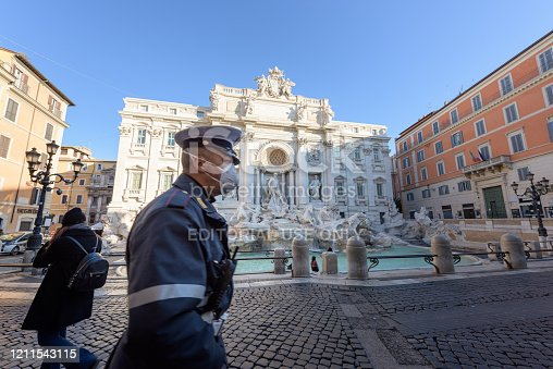 istock Police man wearing a face mask walks across the deserted Trevi Fountain square, Rome, Italy 1211543115