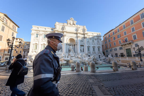Police man wearing a face mask walks across the deserted Trevi Fountain square, Rome, Italy ROME, ITALY - 10 March 2020: A city Police man wearing a face mask walks across the deserted Trevi Fountain square, Rome, Italy. As of today, the Italian government decreeted a nationwide quarantine, with travel and gatherings bans, limited opening hours for shops and venues, and emergency health measures following the CoVid-19 epidemic. Tourism has collapsed as a result. lazio stock pictures, royalty-free photos & images