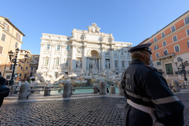 Police man wearing a face mask walks across the deserted Trevi Fountain square, Rome, Italy stock photo