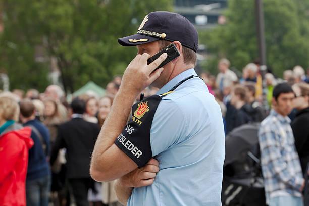 police man with mobile phone. - oslo city hall stockfoto's en -beelden