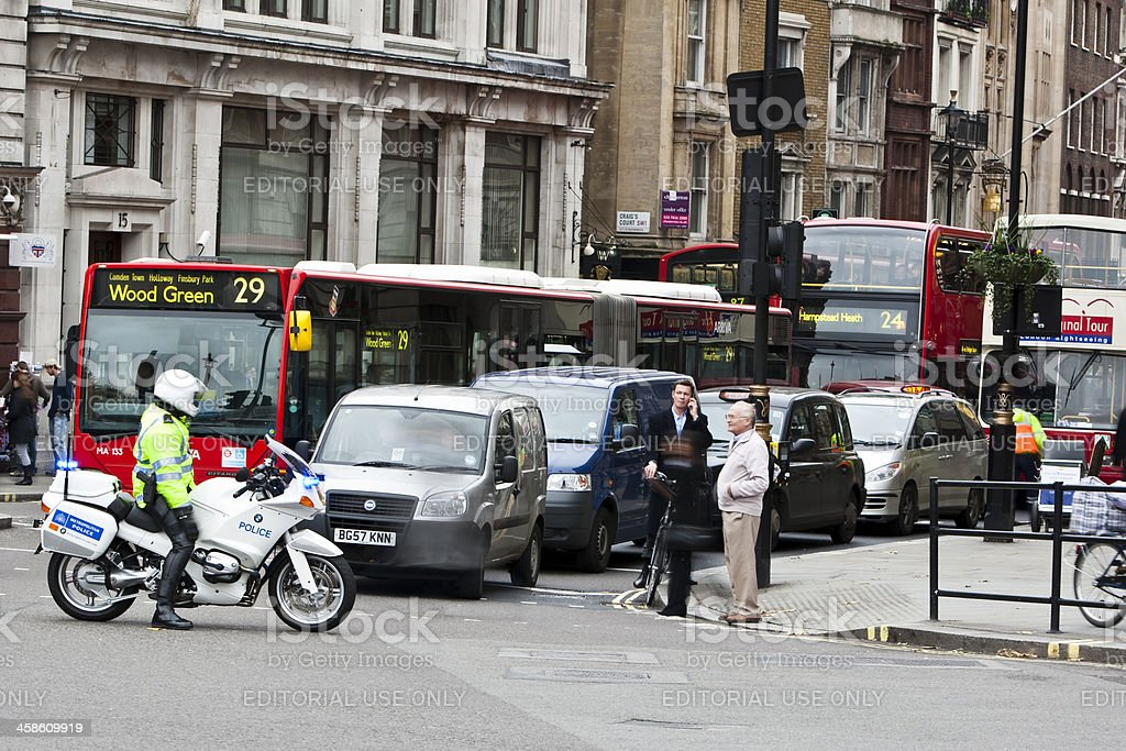 Police Motorcyclist Stopping Traffic at Junction in London stock photo