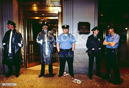 May 1985. NYC. Police of the city of New York, with 1980s attitude. All very different way from the police today. Standing at the door of the Marriot Essex House Hotel. Mustache, belly, poor body posture, camera smiles. Night .Flash